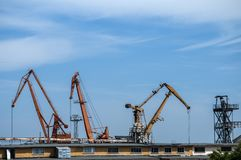Industrial scene on sky background. Industrial scene with crane and river port facilities on blue sky background royalty free stock photos