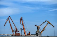 Industrial scene on sky background. Industrial scene with crane and river port facilities on blue sky background stock photos