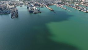 Industrial seaport, top view. Port cranes and cargo ships and barges. Loading and shipment of cargo at the port. View of the sea cargo port with a bird`s eye stock footage