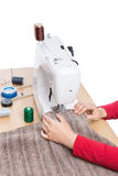 Industrial sewing machine and hand seamstress. Royalty Free Stock Photography