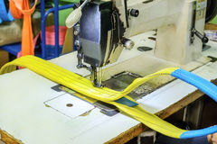 Industrial sewing machine sews a ratchet strap. Stock Images