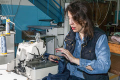 Industrial sewing machines with sewing machine operator Stock Image
