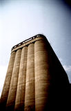 Industrial silo. Tall cereal storage silo, perspective view with vignette and dramatic colors. Film scan Stock Photography