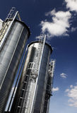 Industrial silo tanks. Two large industrial silo tanks against the blue sky Royalty Free Stock Photos