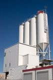 Industrial silos. White industrial silos against a clear blue sky Royalty Free Stock Photo