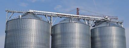 Industrial silos against the  blue sky. Industrial silos in the fields against the sky stock photos