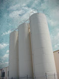 Industrial silos with textured aged sky Royalty Free Stock Photos