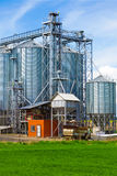 Industrial silos under blue sky, in the field Royalty Free Stock Photo