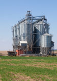 Industrial silos under blue sky, in the field Royalty Free Stock Images