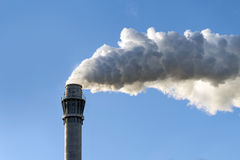 Industrial smoke from a chimney against the clear blue sky, copy Stock Image