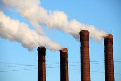 Industrial smoke from chimney on a blue sky Stock Photo