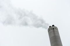 Industrial smoke from chimney on grey sky stock photography