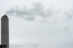 Industrial smoke from chimney on grey sky royalty free stock photography