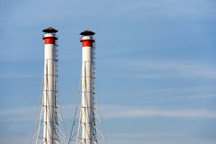 Industrial smoke pipes over blue sky vertical view Royalty Free Stock Photography
