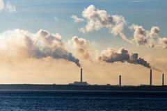 Industrial smoke from a plant on the shore of a lake Stock Photography