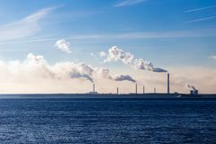 Industrial smoke from a plant on the shore of a lake Stock Photos