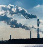 Industrial smoke from a plant on the shore of a lake Stock Images