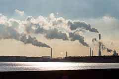 Industrial smoke from a plant on the shore of a lake Stock Photo