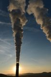 Industrial smoke stack at sunset Stock Images