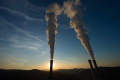 Industrial smoke stack at sunset Stock Image