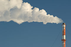 Industrial smokestack. Smoke billows from a smokestack against a blue sky Stock Photography