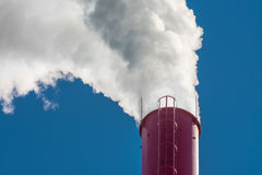 Industrial smokestack. Dense white smoke ascending from red smokestack on blue sky Stock Photography