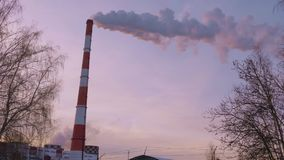 Heat generation station with smoke and tube at sky background winter evening. Industrial smoking pipes at heat power station on background sky and bare trees stock footage