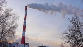 Industrial smoking pipes at heat power station on background sky and bare trees. Fuming industrial chimney stack in winter sky stock video footage
