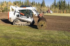 Industrial sod installation with tractor. City park playground sod installation in industrial scale using big sod rolls and machinery stock photography