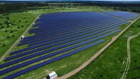Industrial solar energy farm producing clean renewable energy from sun. Aerial view rows of solar panels on green field. Solar station generating green energy stock footage