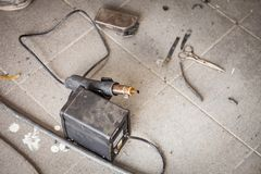 Industrial soldering gun of black color on the floor among dust and tools for heating and melting plastic during the connection of stock photography