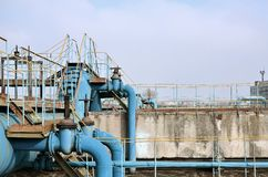 Industrial space with lots of pipes and communications on a background of blue sky. old water treatment plant on the city`s wate. R supply enterprise. Kharkov Royalty Free Stock Photos