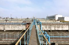 Industrial space with lots of pipes and communications on a background of blue sky. old water treatment plant on the city`s wate. R supply enterprise. Kharkov Royalty Free Stock Photography