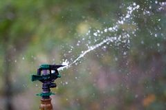 An industrial sprinkler shooting a jet of water with selective f Royalty Free Stock Images