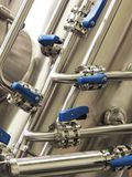 Industrial stainless steel pipe work with valves and blue handles. Industrial stainless steel pipe work with valves and blue polymer handles royalty free stock images