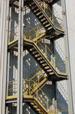 Industrial staircase. A fire escape staircase running down the outside of a factory Stock Image