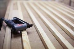 Industrial stapler on wooden slats door frame. royalty free stock image