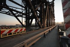 Industrial steel bridge structure with walkway. Industrial steel structure bridge, deck and pedestrian walkway at sunset with an urban city scape in the distance stock image