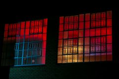 Industrial steel window frames of night club or venue. Red purple blue black light behind industrial steel window frames of night club or venue Stock Image