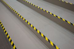 Industrial striped road or step warning on grey walkway. Yellow-black pattern royalty free stock images