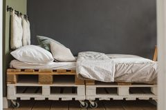 Industrial style bedroom recycled pallet bed frame. A industrial style bedroom with recycled pallet bed frame designs Stock Photography