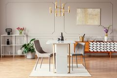 Industrial style, golden pendant light above an exceptional marble table in a trendy dining room interior. With eclectic decor stock photos