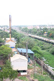 Industrial Suburb of Chennai, Indian City. A metro passenger train passing near to Industrial area at Chennai suburban city, India Stock Photos