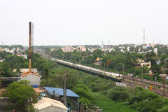 Industrial Suburb of Chennai, Indian City. A metro passenger train passing near to Industrial area at Chennai suburban city, India Royalty Free Stock Image