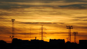 Industrial sunset. With power lines and golden sky Stock Photos