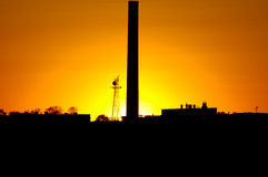 Industrial Sunset. Sunset silhouetting a smokestack from a factory royalty free stock photos