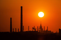 Industrial sunset. Beautiful orange sunset of industrial plant with tall chimneys Royalty Free Stock Image