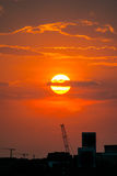 Industrial Cityscape. A sunset with industrial buildings and a construction crane in the city Royalty Free Stock Photography