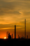 Industrial Sunset with Copy Space. Industrial processing towers rise into the vivid orange sunset Stock Photo