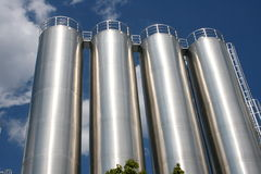 Industrial tanks. Four silver industrial tanks with blue sky royalty free stock images